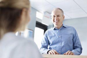 A man smiling at a dental employee.