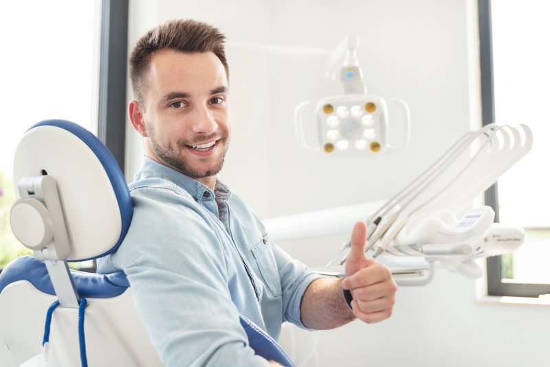 Male dental patient giving a thumbs up